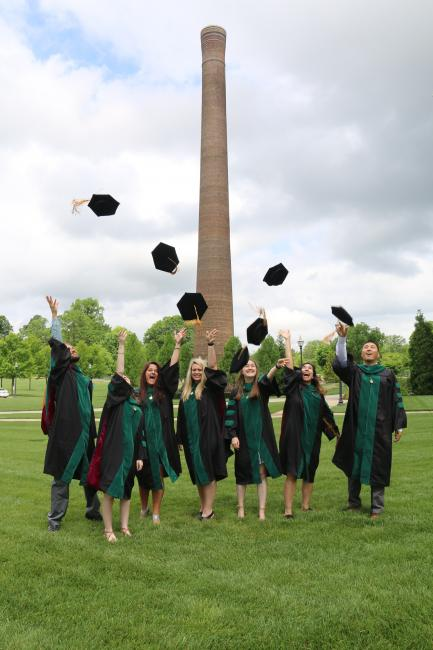 VCOM Carolinas graduates throw their caps into the air in front of the historic campus smoke stack