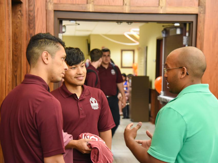 instructor speaks with new students outside classroom