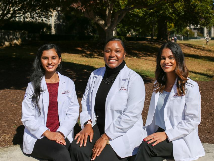 three medical students wear their white coats following the ceremony